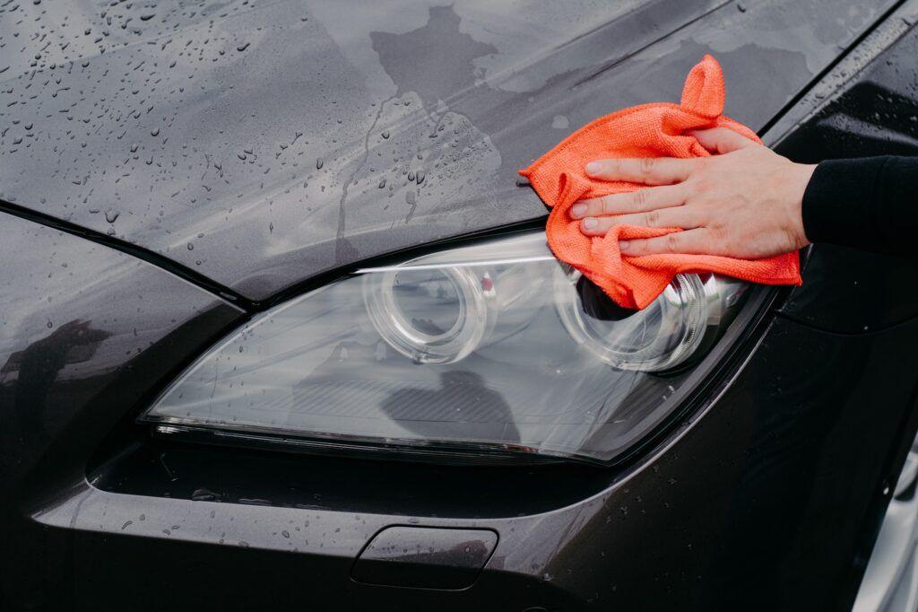 Wet black automobile cleanes at car wash